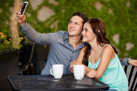 Young attractive couple taking a photo with a cell phone during their first date at a cafe photo