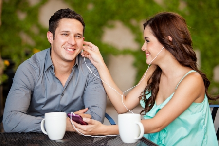 Cute young woman and her date listening to some music together at a terrace photo