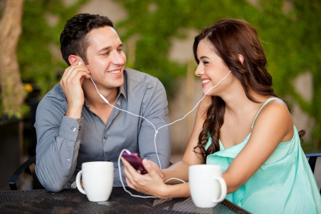 Happy Hispanic couple listening to some music while having coffee on a date photo
