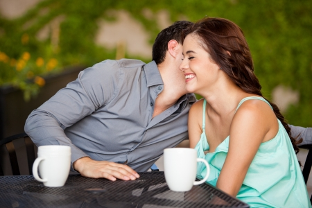 Young man leaning in and whispering something to his date s ear while drinking coffee at a terrace photo