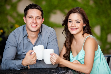 Attractive Hispanic couple drinking coffee and smiling during a date at a terrace