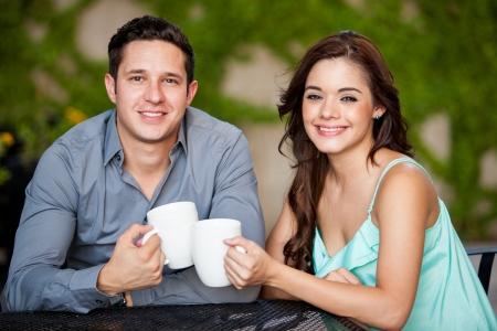 mujer tomando cafe: Hispanico atractivo joven bebiendo caf� y sonriente durante una cita en una terraza