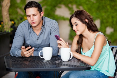 Young couple passing the time by using their cell phones on a bad date