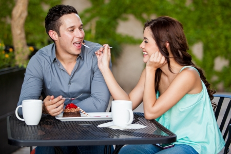 Cute young couple sharing cake at a restaurant terrace photo