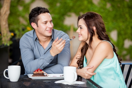 야외 레스토랑에서 그의 아름다운 날짜와 함께 케이크를 공유하는 잘 생긴 젊은 남자