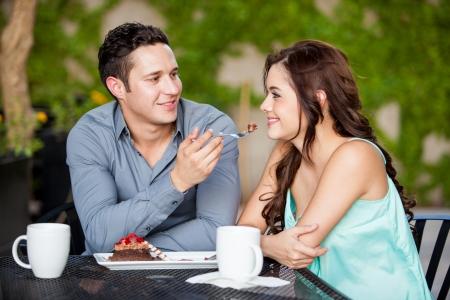 pareja comiendo: Hombre joven hermoso pastel de compartir con su pareja hermosa en un restaurante al aire libre