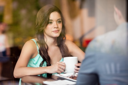 Gorgeous brunette having coffee with a male friend at cafe photo
