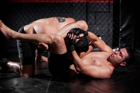 Strong Latin MMA fighter grappling and controlling his opponent during a fight