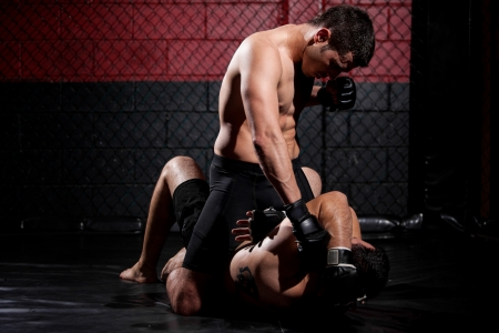 mixed martial arts: Stronger mixed martial arts fighter holding his opponent down and winning the fight Stock Photo