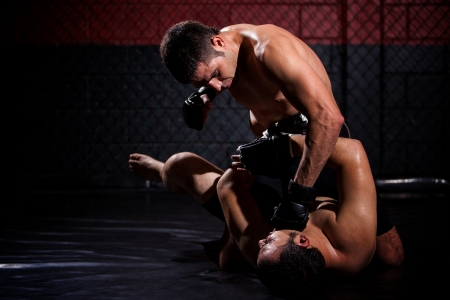 Strong MMA fighter holding his rival down and throwing punches at him during a fight  With plenty of copy space Stock Photo