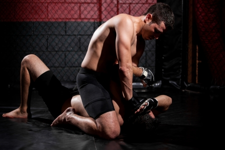mixed martial arts: Strong mixed martial arts fighter holding his rival down and trying to punch him Stock Photo