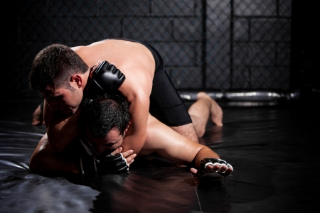 mixed martial arts: Strong MMA fighter grappling his opponent and forcing him to tap out Stock Photo