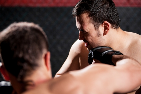 the opponent: Point of view of a MMA fighter punching his opponent during a fight in a cage Stock Photo