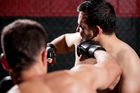 Point of view of a MMA fighter punching his opponent during a fight in a cage Stock Photo