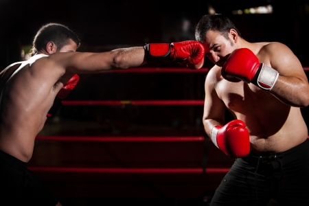 punching: Boxer using some jabs to punch his opponent and win the box match Stock Photo