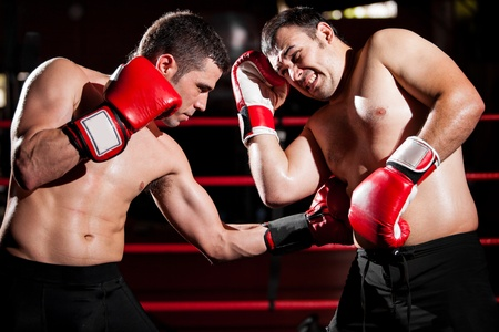 Latin boxer punching his rival in the ribs during a box fight photo