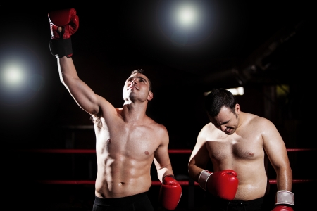 boxing match: Winner of a boxing match celebrating next to his defeated opponent  With lens flare and a more dramatic look
