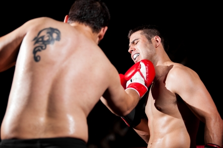 the opponent: Strong boxer being punched by his opponent with an uppercut Stock Photo