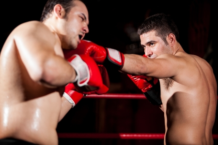 the opponent: Stronger boxer punching his opponent during a fight