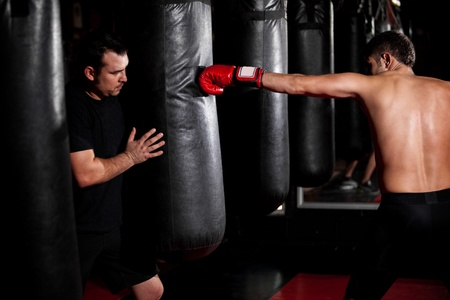 stance: Young Boxer training with his coach on a punching bag at a gym Stock Photo