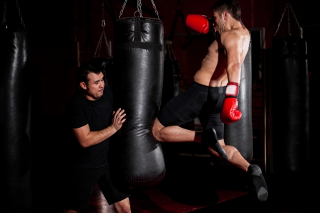 athlete: Latin Fighter throwing a kick at a punching bag while his coach gives him some direction
