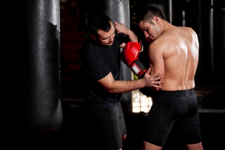 mixed martial arts: Male boxer getting some tips on his technique from his coach at a gym Stock Photo