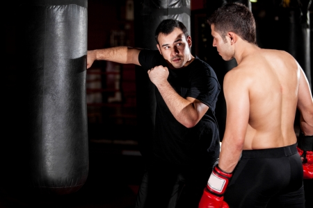 mixed martial arts: Latin Boxer and his coach practicing some moves on a punching bag at a gym Stock Photo