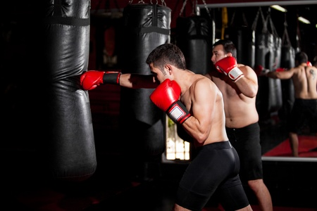 punching bag: Latin Boxers doing some training on a punching bag at a gym
