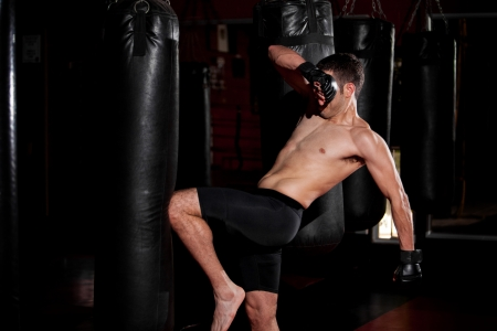 Mixed martial arts fighter kicking a punching bag with his knee during training photo