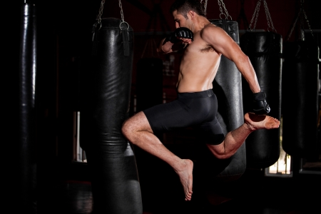 Strong mixed martial arts fighter practicing some knee kicks on a punching bag at a gym photo