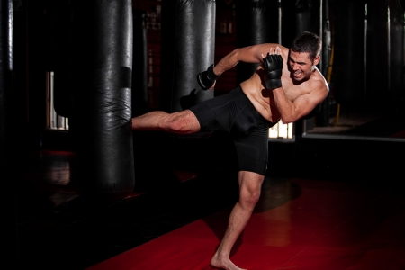 mixed martial arts: Hispanic MMA Fighter practicing some kicks with a punching bag at a gym