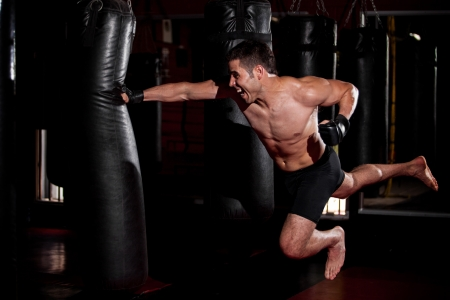 punching bag: Fearles MMA Fighter practicing his superman punch on a punching bat at a gym