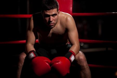 boxer: Dram�tico retrato de un boxeador joven hispano sentado en su esquina del ring con un poco de espacio de la copia Foto de archivo