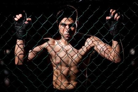 mixed martial arts: Dram�tico retrato de un combatiente de MMA el acaparamiento de la lucha de la jaula e intimidar a sus oponentes
