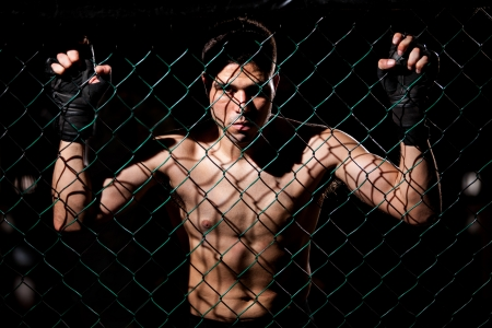 Dramatic portrait of a MMA Fighter grabbing the fighting cage and intimidating his opponents photo