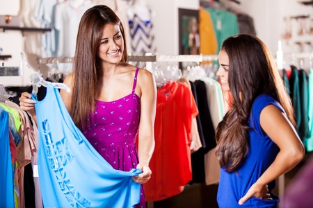 opinions: Pretty female friends shopping some clothes together in a store Stock Photo