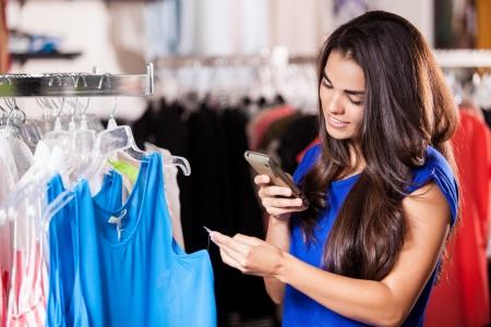 etiquetas de ropa: Mujer bonita latina tomar una instant�nea de una etiqueta de precio en una tienda de ropa