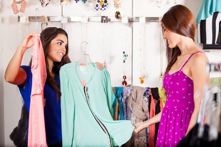 better: Cute girl helping her friend decide on which blouse would look better on her Stock Photo