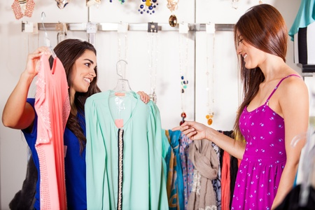 help: Cute young woman asking her friend s opinion about a couple of blouses