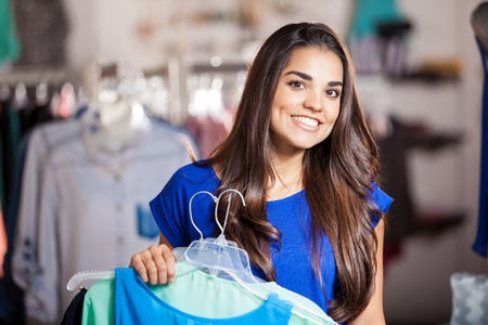 wider: Wider shot of a happy girl carrying a few dresses before trying them on and smiling Stock Photo