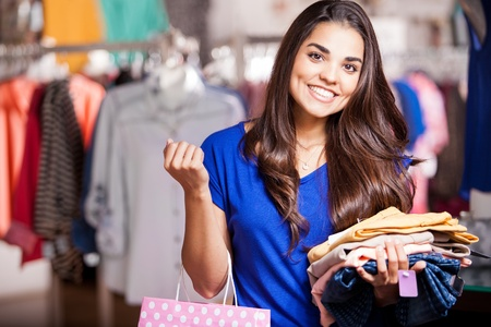 jolie fille: Jolie fille tenant un sac à provisions et quelques vêtements qu'elle veut essayer dans un magasin de vêtements