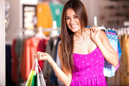 Beautiful happy girl carrying some shopping bags at a clothing store and smiling Stock Photo - 21893537