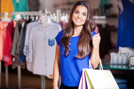 clothing stores: Beautiful Hispanic girl carrying some shopping bags in a clothing store