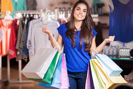 so: Beautiful Latin woman carrying so many shopping bags in a clothing store