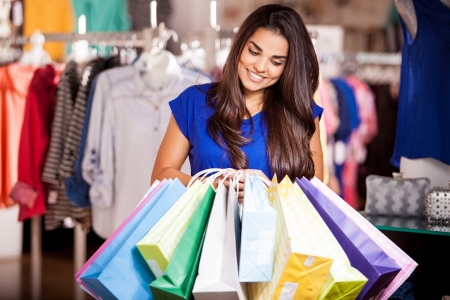 Cute young woman doing some serious shopping and smiling photo