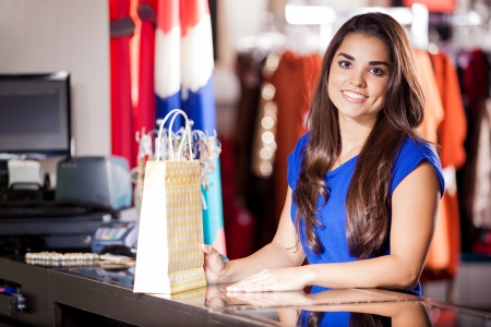 checkout: Happy young woman doing some shopping in a clothing store and smiling