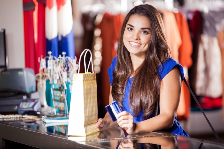 Pretty Hispanic woman buying some clothes with a credit card photo