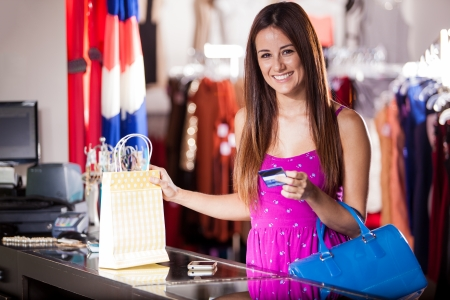 discounts: Pretty Latin woman buying some clothes at a store with a credit card
