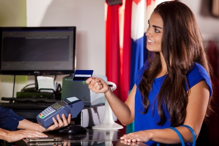 checkout: Cute young woman paying with a credit card in a cash register and smiling
