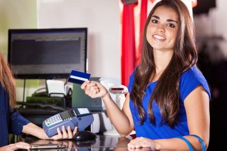 Mooie Spaanse vrouw het betalen met een credit card in een kledingzaak